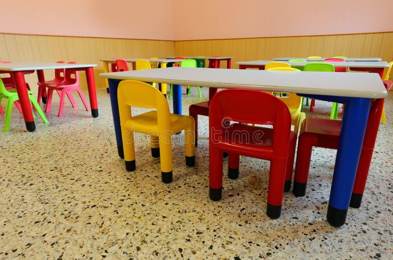Salle de l'école avec petites chaises et tables image stock