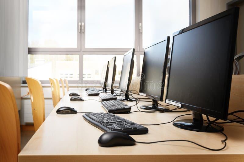 Salle des ordinateurs vide avec des moniteurs et des claviers dans une rangée pour des élèves et des étudiants dans un laboratoir photo stock