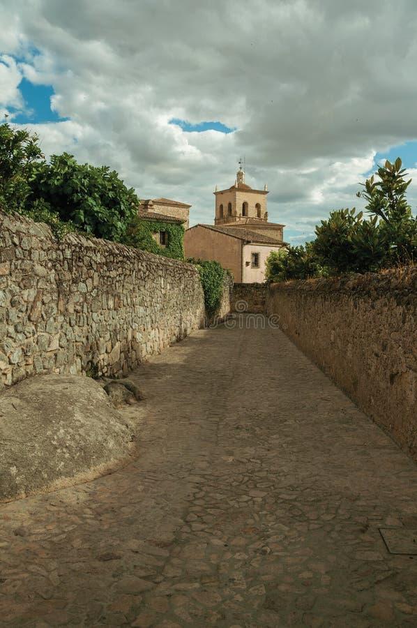 sAlley in un giorno nuvoloso con le pareti di pietra che vanno verso Santa Maria la Mayor Church ed il campanile a Trujillo fotografie stock