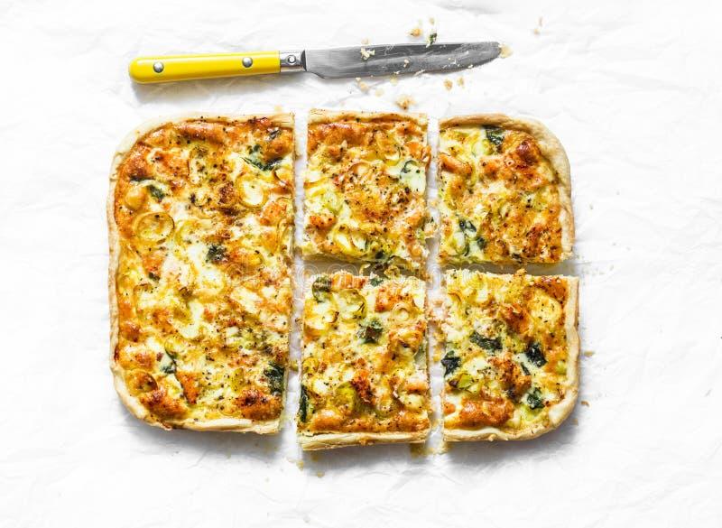Salmões, alho poró, espinafre, galdéria da massa folhada do queijo, torta no fundo claro foto de stock royalty free