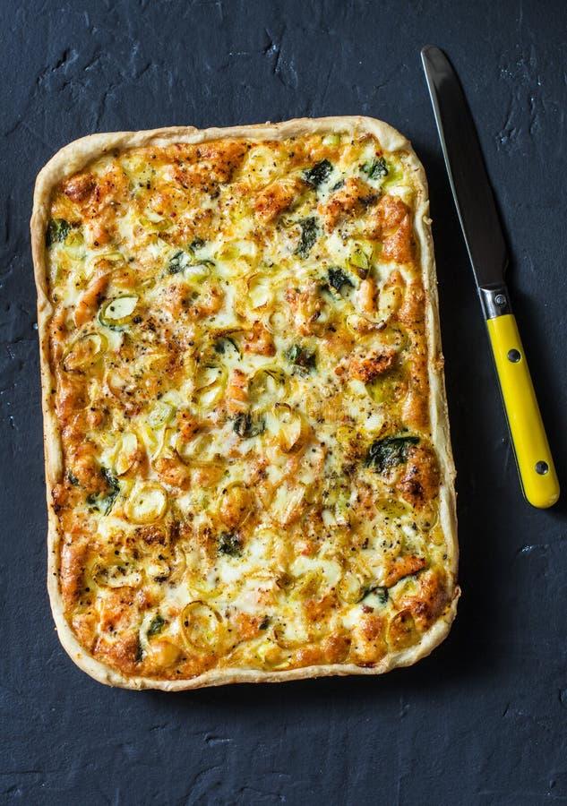 Salmões, alho-porro, espinafre, torta da massa folhada do queijo no fundo escuro imagem de stock