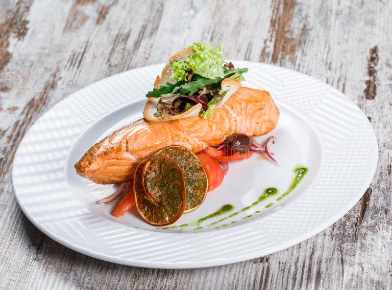 Salm?es cozidos decorados com azeitonas, verdes, tomates na placa sobre o fundo de madeira Prato de peixes quente fotografia de stock royalty free