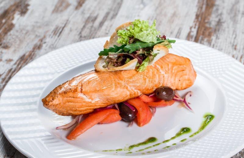Salm?es cozidos decorados com azeitonas, verdes, tomates na placa sobre o fundo de madeira Prato de peixes quente imagens de stock