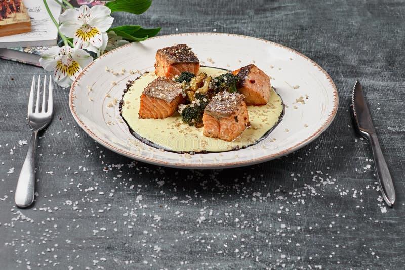 Salmões cozidos dos peixes no molho do açafrão com brócolis Menu dietético Menu dos peixes Marisco - salmão foto de stock
