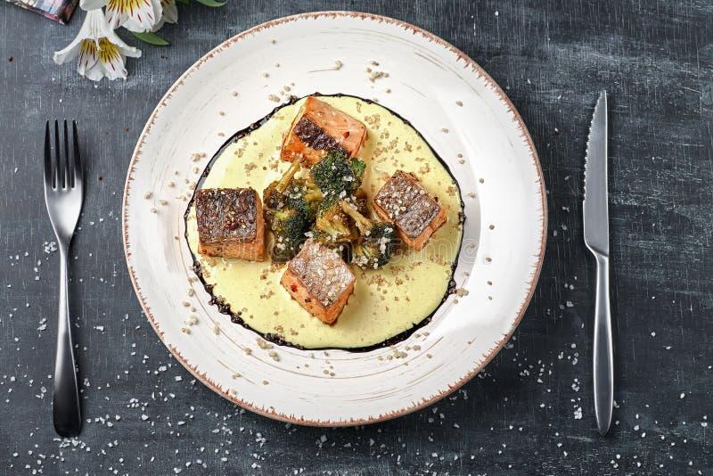 Salmões cozidos dos peixes no molho do açafrão com brócolis Menu dietético Menu dos peixes Marisco - salmão foto de stock royalty free