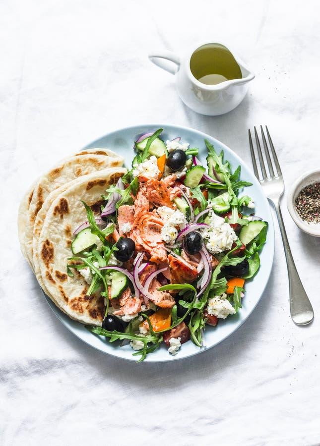 Salm?es cozidos, tomate, pepino, foguete, salada grega em um fundo claro, vista superior do queijo de feta Alimento mediterr?neo  foto de stock