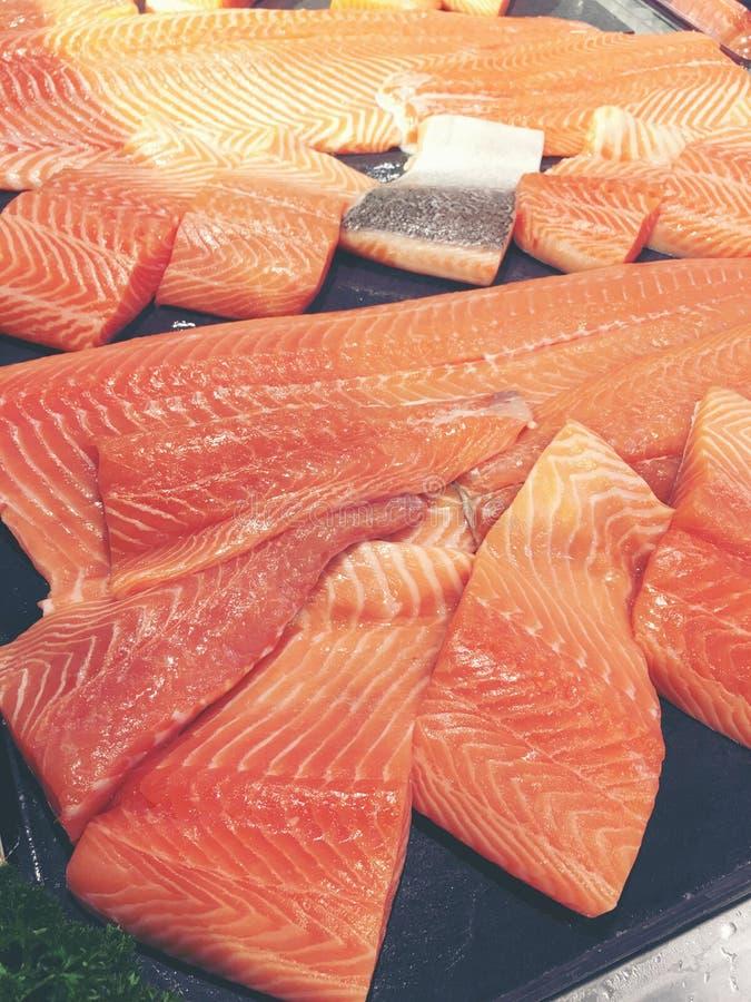 Salmões crus cortados ou salmões frescos O salmão enfaixa para a venda no mercado indicado com um efeito dos retalhos Muitos peix imagens de stock