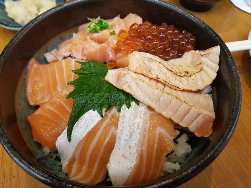 Salmões crus deslizados com arroz japonês foto de stock