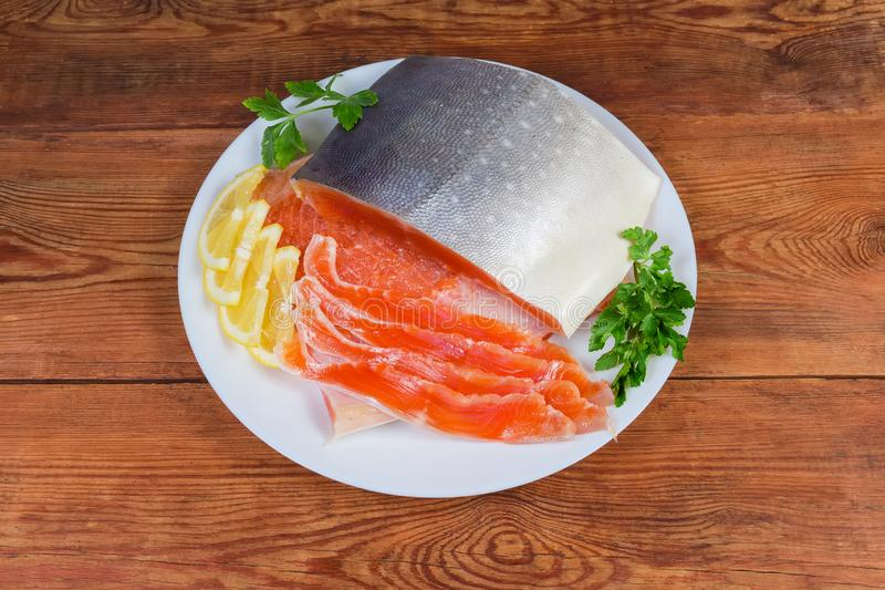 Salmerino alpino salato parzialmente affettato sul piatto sulla tavola rustica fotografie stock libere da diritti