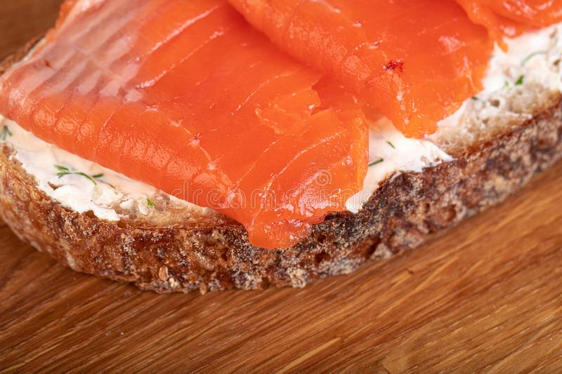 Salmom sandwich. Sandwich with salmon on wooden board stock photo