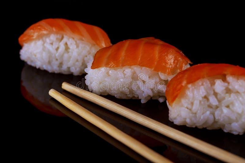 Salmon палочки nigiri суш над черной предпосылкой стоковое изображение