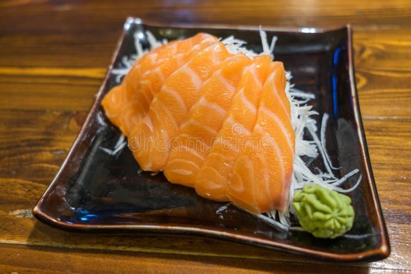 Salmon сасими на черной керамической плите с частью Wasabi стоковое фото