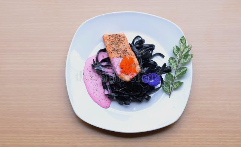Salmon стейк при соус бураков макаронных изделий чернил кальмара cream жаря tobiko косуль рыб стоковое фото