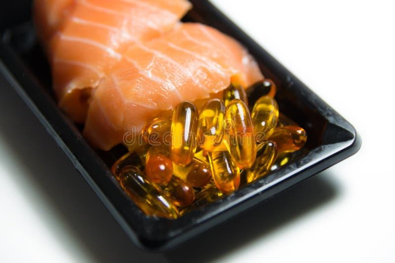 Salmon суши служили при изолированный крупный план пилюлек рыбьего жира стоковые фотографии rf