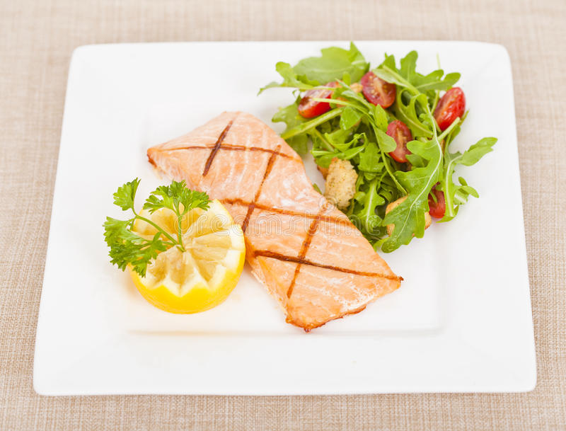 Salmon. Fresh cooked salmon fillet with arugula salad stock photos