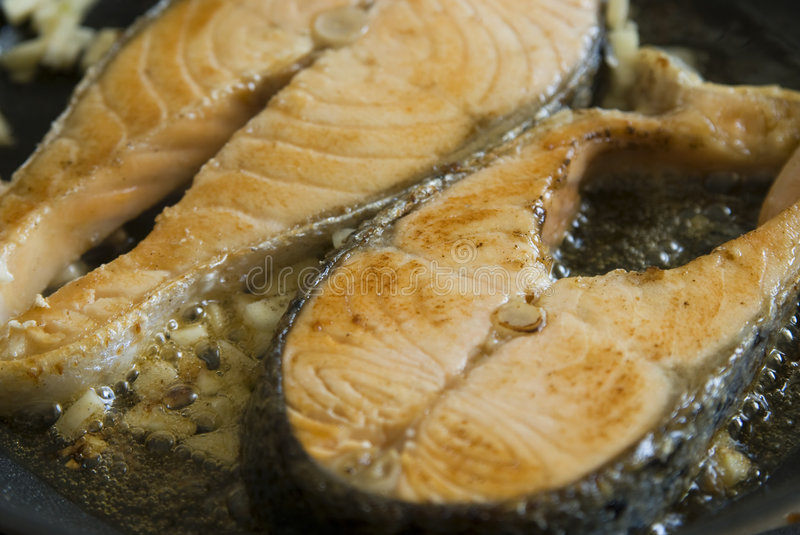 Salmon. Fillet salmon in a frying pan royalty free stock photography