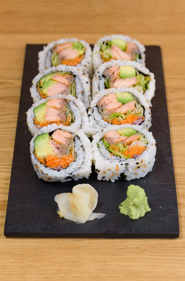 Salmon, avocado and carrot sushi roll served on a slate plate with ginger and wasabi stock photos