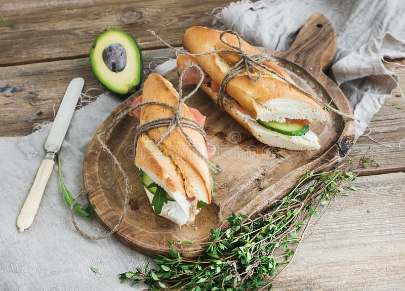 Salmon, avocado and thyme sandwiches in baguette tied up with decoration rope on a rustic wooden board over rough wood background. Salmon and avocado sandwiches royalty free stock image