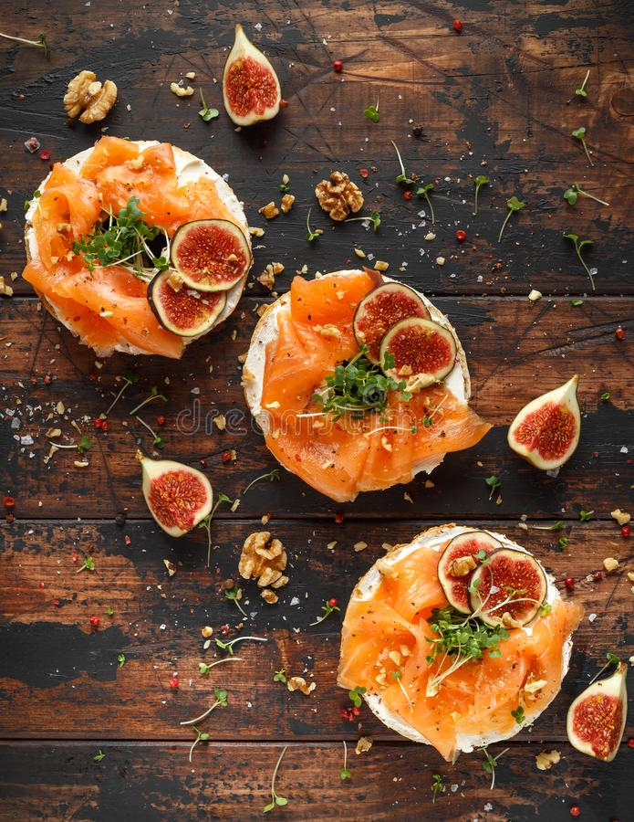 Salmon Bagel Sandwich with figs, cress salad, walnuts, cream cheese and grain on rustic wooden background. healthy royalty free stock image