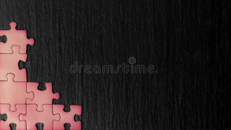 Salmon color puzzle in the corner of the image on a black natural stone background of slate. A frame with an empty space for your. Description stock photos
