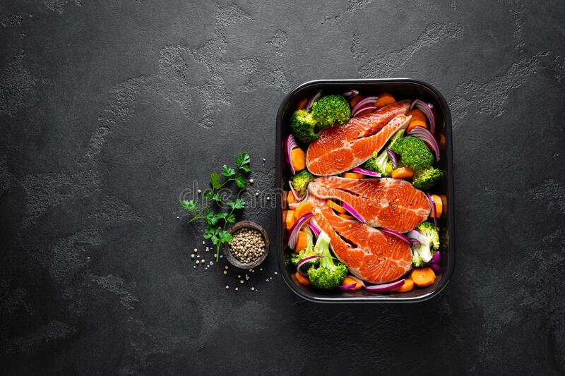 Salmon. Cooking fresh raw salmon fish steaks with vegetables, broccoli, carrot and onion on black background stock image