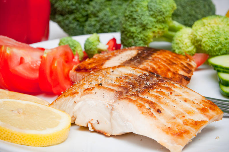 Salmon diet food. Grilled salmon diet fish food closeup with vegetables in background stock images