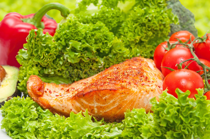 Salmon diet food salad. Grilled salmon diet fish food salad with tomato and bell pepper vegetables in background royalty free stock photo