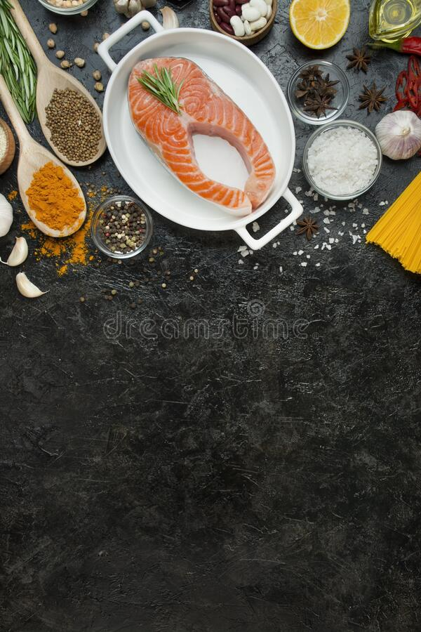 Salmon fillet with aromatic herbs, spices, Italian pasta and vegetables on a dark background. Cooking concept. Culinary background royalty free stock images