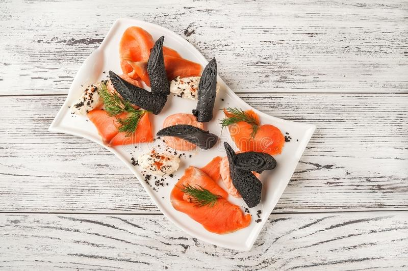 Salmon fillet with black pancakes and sauce close-up. Snack of trout, mozzarella and pancakes on a white plate copy space stock image