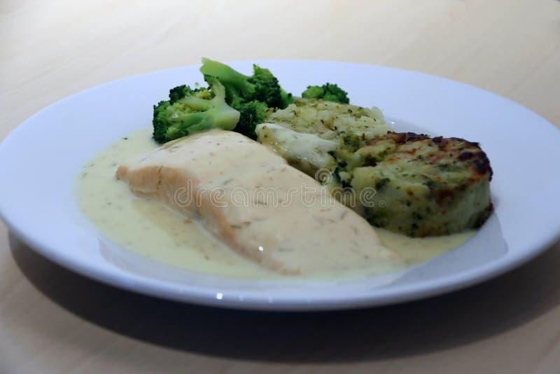 Salmon Fillet con los medallones vegetales, la verdura mezclada, el bróculi verde, el limón y el eneldo sauce en el plato blanco foto de archivo