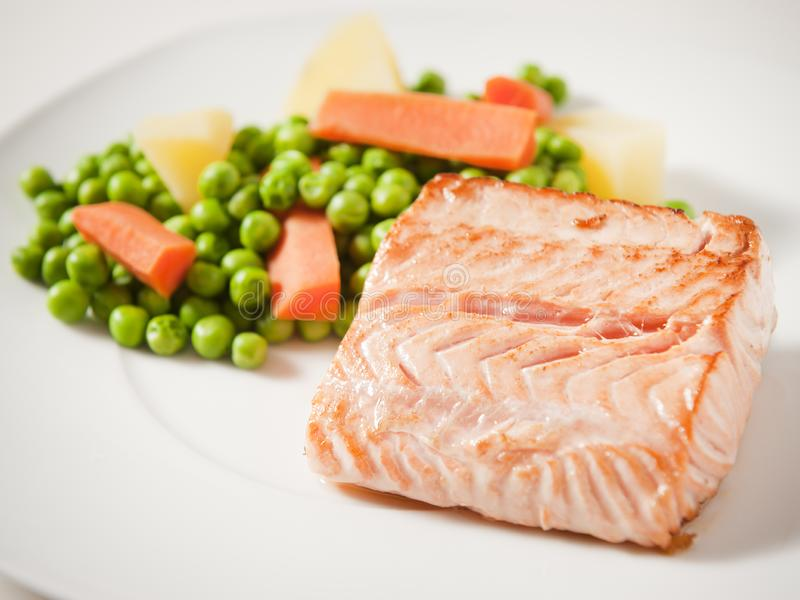 Salmon fillet. With green peas, carrot and potatoes royalty free stock photo