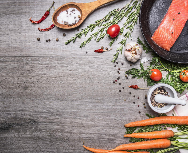 Salmon fillet in a pan with herbs, vegetables and spices place for text,frame wooden rustic background top view stock images