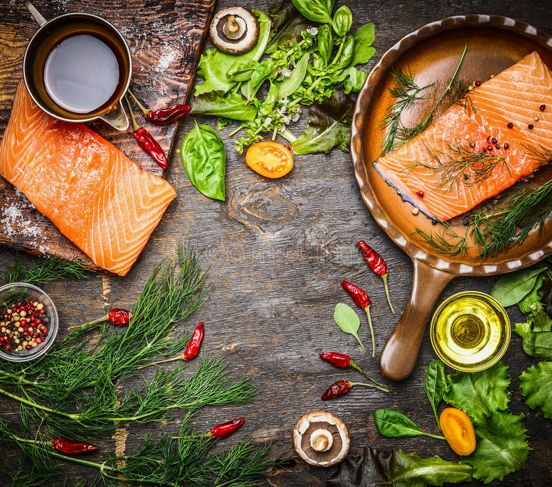 Salmon fillet on rustic kitchen table with fresh ingredients for tasty cooking and frying pan. Wooden background, frame, top view. royalty free stock images