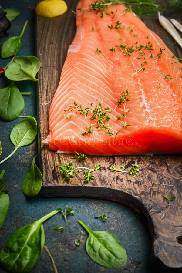 Salmon fillets on cutting board and fresh ingredients for cooking. Close up stock photography