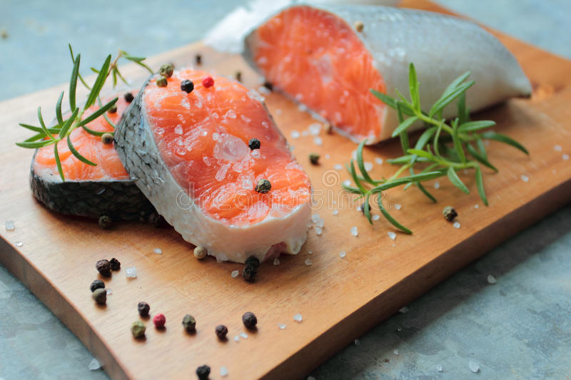 Salmon fillets. With fresh spices on wooden cutting board royalty free stock image