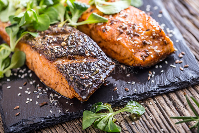 Salmon fillets. Grilled salmon, sesame seeds herb decorationon on vintage pan or black slate board. Fish roasted on an old wooden table.Studio shot royalty free stock image