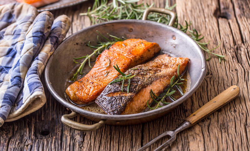 Salmon fillets. Grilled salmon, sesame seeds herb decorationon on vintage pan or black slate board. Fish roasted on an old wooden table.Studio shot royalty free stock images