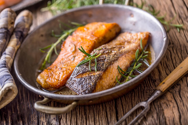 Salmon fillets. Grilled salmon, sesame seeds herb decorationon on vintage pan or black slate board. Fish roasted on an old wooden table.Studio shot stock photography