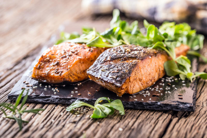 Salmon fillets. Grilled salmon, sesame seeds herb decorationon on vintage pan or black slate board. Fish roasted on an old wooden table.Studio shot royalty free stock photos