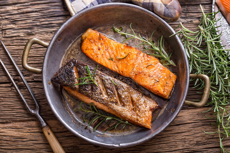 Salmon fillets. Grilled salmon, sesame seeds herb decorationon on vintage pan or black slate board. Fish roasted on an old wooden table.Studio shot royalty free stock photo