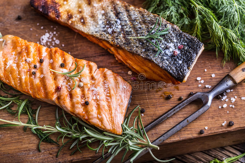 Salmon fillets. Grilled salmon, sesame seeds herb decorationon on vintage pan or black slate board. Fish roasted on an old wooden table.Studio shot royalty free stock photography