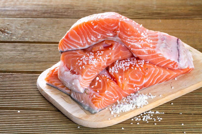 Salmon fillets with salt. On a wooden background royalty free stock image