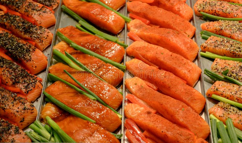 Salmon fillets seasoned many different ways. Salmon fillets seasoned many different ways are part of a healthy and delicious meal royalty free stock photos