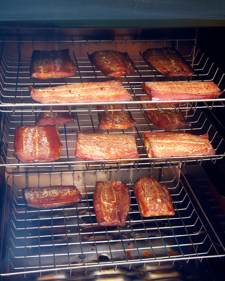 Salmon fillets smoking in a smoker stock images
