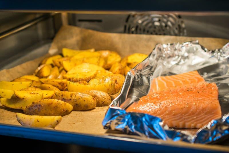 Salmon Fish avec des pommes de terre de romarin, cuites au four dans le four photo libre de droits