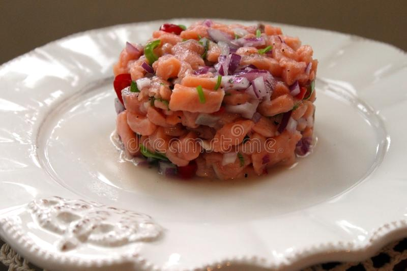 Salmon fish ceviche cooking ring serving on white plate close up. Traditional Peruvian dish royalty free stock images