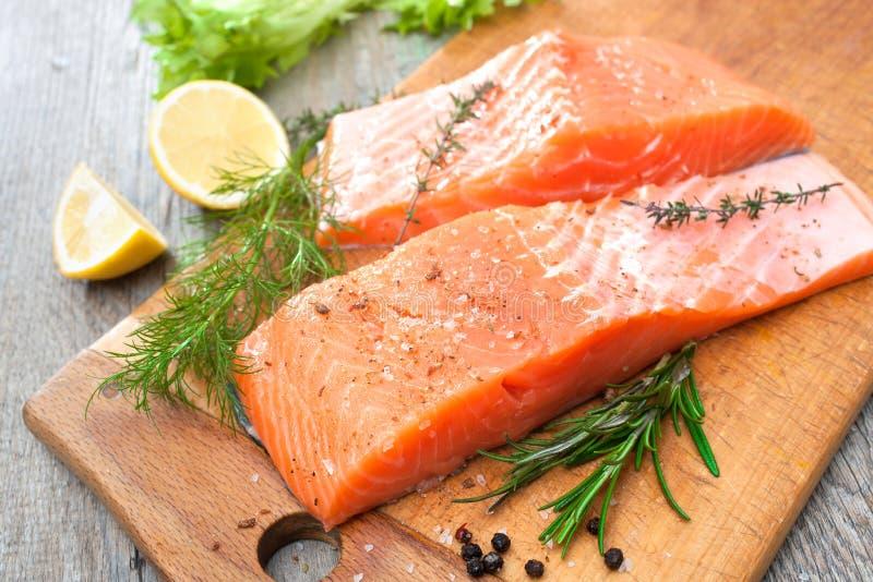 Salmon fish fillet with fresh herbs. Raw salmon fish fillet with fresh herbs on cutting board