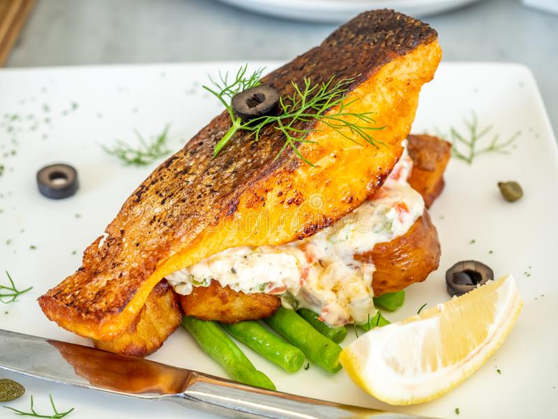 Salmon fish fillet steak served with asparagus, cream salad and lemon stock image