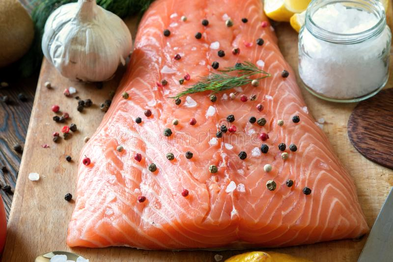 Fresh delicious salmon fillet with aromatic herbs, spices, garlic, lemon on dark background. Top view. Closeup. stock photography