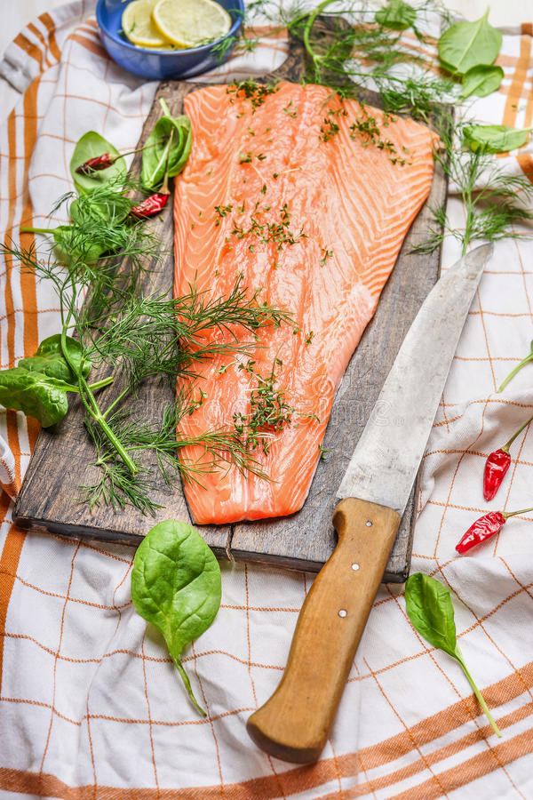 Salmon fish fillets on cutting board with knife and fresh seasoning and spices on plaid kitchen table-napkin. stock image
